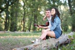 Jeunes couples reposant sur un identifiez-vous la forêt et jouant la guitare, nature d'été, sentiments romantiques images stock