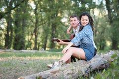Jeunes couples reposant sur un identifiez-vous la forêt et jouant la guitare, nature d'été, sentiments romantiques photographie stock