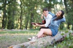 Jeunes couples reposant sur un identifiez-vous la forêt et jouant la guitare, nature d'été, sentiments romantiques photos libres de droits