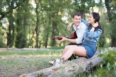Jeunes couples reposant sur un identifiez-vous la forêt et jouant la guitare, nature d'été, sentiments romantiques photographie stock libre de droits
