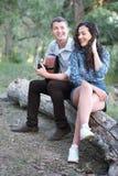 Jeunes couples reposant sur un identifiez-vous la forêt et jouant la guitare, nature d'été, sentiments romantiques photo stock