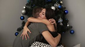 Jeunes couples restant à la maison ensemble la soirée de vacances et se reposant sur le plancher près de l'arbre de Noël sur le p banque de vidéos