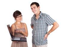 Jeunes couples retenant un ordinateur portatif et un sourire Images libres de droits