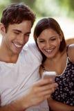Jeunes couples riant avec un smartphone photographie stock libre de droits