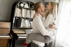 Jeunes couples riant, embrassant et ayant l'amusement dans la chambre Photographie stock