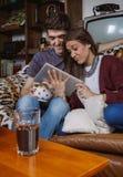 Jeunes couples riant et regardant la séance de comprimé Image stock