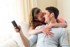 Jeunes couples riant tout en regardant la télévision Photographie stock libre de droits