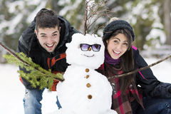 Jeunes couples riants étreignant le bonhomme de neige Photo libre de droits