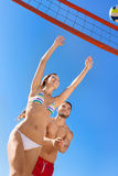 Jeunes couples riants jouant le volleyball Photographie stock