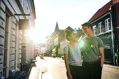 Jeunes couples riants marchant ensemble le long d'un trottoir de ville photos stock