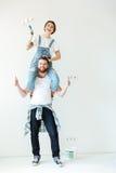 Jeunes couples riants tenant des rouleaux de peinture et regardant l'appareil-photo Image stock