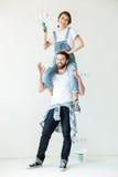 Jeunes couples riants tenant des rouleaux de peinture et regardant l'appareil-photo Image libre de droits