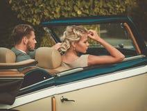 Jeunes couples riches dans un convertible classique Images libres de droits