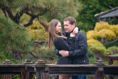 Jeunes couples romantiques étreignant sur le pont dans le jardin japonais Image stock