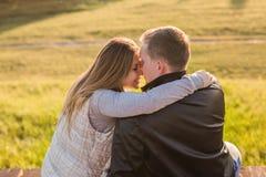 Jeunes couples romantiques appréciant la nature d'automne se reposant dans une étreinte étroite, vue par derrière Photographie stock libre de droits