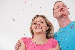 Jeunes couples romantiques célébrant la partie avec des confettis photo libre de droits