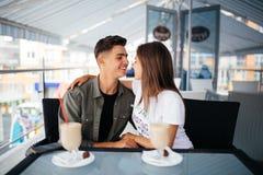 Jeunes couples romantiques dans l'amour embrassant en café Images stock