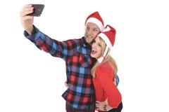 Jeunes couples romantiques dans l'amour prenant la photo de téléphone portable de selfie à Noël Photo libre de droits