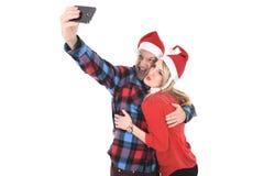 Jeunes couples romantiques dans l'amour prenant la photo de téléphone portable de selfie à Noël Images libres de droits