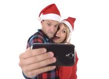Jeunes couples romantiques dans l'amour prenant la photo de téléphone portable de selfie à Noël Photographie stock