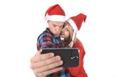 Jeunes couples romantiques dans l'amour prenant la photo de téléphone portable de selfie à Noël Image stock
