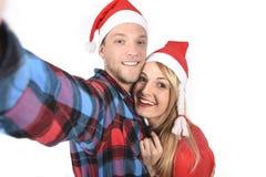 Jeunes couples romantiques dans l'amour prenant la photo de téléphone portable de selfie à Noël Photographie stock libre de droits