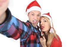 Jeunes couples romantiques dans l'amour prenant la photo de téléphone portable de selfie à Noël Photos stock