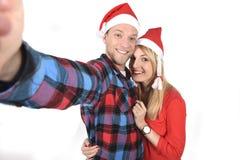 Jeunes couples romantiques dans l'amour prenant la photo de téléphone portable de selfie à Noël Image libre de droits