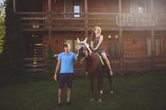 Jeunes couples romantiques dans l'amour, une promenade sur un cheval sur le fond de nature et hôtel en bois de style campagnard J Image libre de droits
