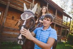Jeunes couples romantiques dans l'amour, une promenade sur un cheval sur le fond de nature et hôtel en bois de style campagnard J Photographie stock
