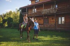 Jeunes couples romantiques dans l'amour, une promenade sur un cheval sur le fond de nature et hôtel en bois de style campagnard J Images libres de droits