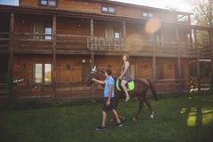 Jeunes couples romantiques dans l'amour, une promenade sur un cheval sur le fond de nature et hôtel en bois de style campagnard J Photo stock