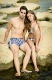 Jeunes couples romantiques dans le costume de natation sur des roches photographie stock