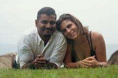 Jeunes couples romantiques de métis se situant en parc sur l'herbe verte Image libre de droits