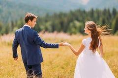 Jeunes couples romantiques de mariage marchant sur le champ ensoleillé avec le fond de forêt Photographie stock libre de droits
