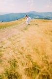 Jeunes couples romantiques de mariage posant sur le champ ensoleillé d'or venteux avec Forest Hills éloigné comme fond Image stock