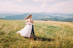 Jeunes couples romantiques de mariage posant sur le champ ensoleillé venteux avec Forest Hills éloigné comme fond Photo libre de droits