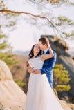 Jeunes couples romantiques de nouveaux mariés étreignant au soleil sur la falaise rocheuse Image libre de droits