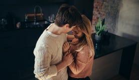 Jeunes couples romantiques embrassant dans la cuisine à la maison Images stock