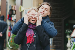 Jeunes couples romantiques extérieurs L'homme couvre ses yeux d'amie faisant une surprise Images stock