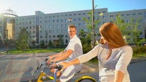 Jeunes couples romantiques heureux faisant un cycle heureusement ensemble par une rue ensoleillée dans l'été dehors Type et fille clips vidéos