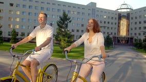 Jeunes couples romantiques heureux faisant un cycle heureusement ensemble par une rue ensoleillée dans l'été dehors Type et fille banque de vidéos