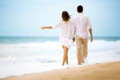 Jeunes couples romantiques heureux marchant à la plage Image libre de droits