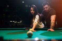 Jeunes couples romantiques jouant le jeu de billard Image libre de droits