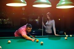 Jeunes couples romantiques jouant le jeu de billard Image stock
