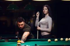 Jeunes couples romantiques jouant le jeu de billard Photos stock