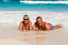 Jeunes couples romantiques s'étendant sur la plage sablonneuse Images stock