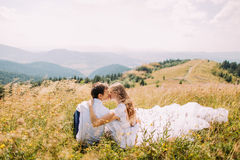 Jeunes couples romantiques se reposant dans l'herbe au champ ensoleillé jaune avec Forest Hills éloigné comme fond Photos stock