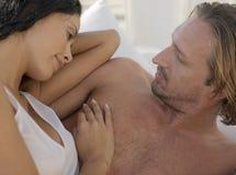 Jeunes couples romantiques se situant dans le lit Images libres de droits