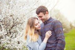 Jeunes couples romantiques se tenant devant le TR de floraison merveilleux Photo stock